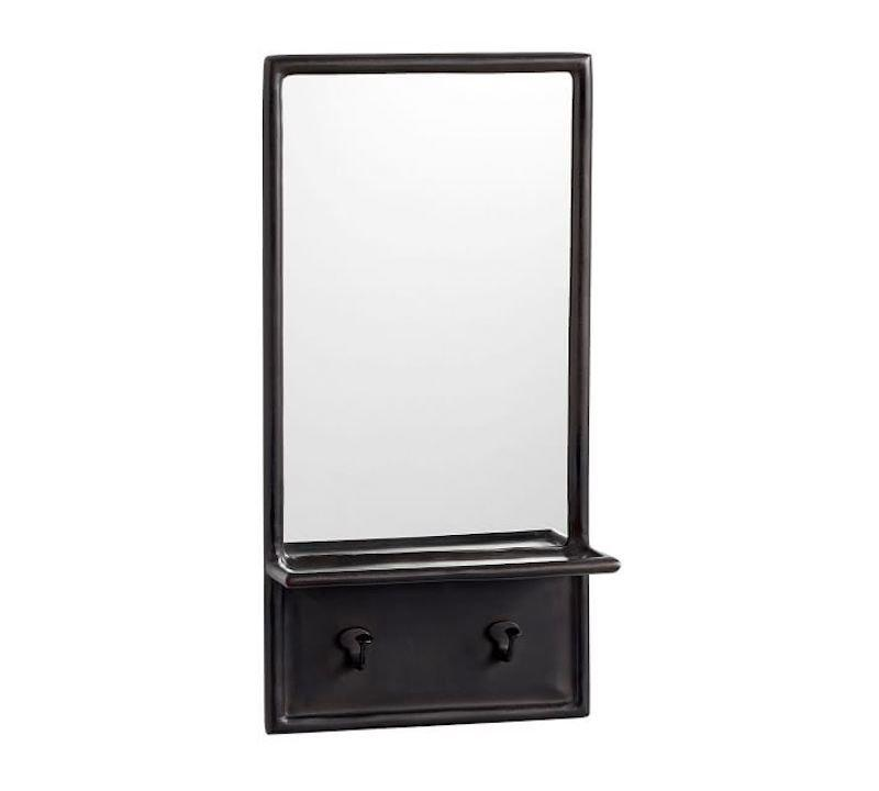"""<p>If your """"foyer"""" is really nothing more than a small wall next to your front door, this mirror with hooks will create a perfectly organized drop zone. Leave your keys on the shelf, and hang your coat and scarf on the hooks so you can grab them on your way out the door. </p> <p><strong>To buy: </strong>$99, <a href=""""http://pottery-barn.7eer.net/c/249354/267848/4332?subId1=RS%2CHere%2527sExactlyHowtoDecorateaSmallEntryway%2Ckholdefehr1271%2CDEC%2CIMA%2C684980%2C201911%2CI&u=https%3A%2F%2Fwww.potterybarn.com%2Fproducts%2Femory-entryway-mirror-with-hooks%2F%3FcatalogId%3D84%26sku%3D8186779"""" target=""""_blank"""">potterybarn.com</a>. </p>"""