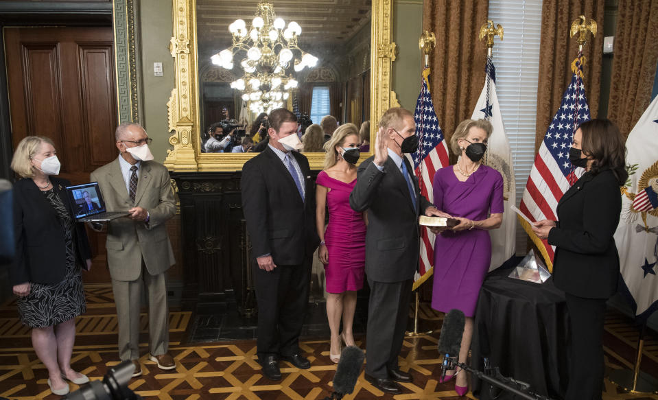 In this photo provided by NASA, former U.S. Sen. Bill Nelson, is ceremonially sworn-in as the 14th NASA Administrator by Vice President Kamala Harris, as his wife, Grace Nelson, holds their family Bible, accompanied by son, Bill Nelson Jr., third from left, and Nan Ellen Nelson, fourth from left, at the Ceremonial Office in the Old Executive Office Building in Washington on Monday, May 3, 2021. A moon rock collected by astronaut John Young during the Apollo 16 mission was on display and former NASA Administrators Jim Bridenstine (virtually on laptop) and Charles Bolden, second from left, were also present. (Aubrey Gemignani/NASA via AP)