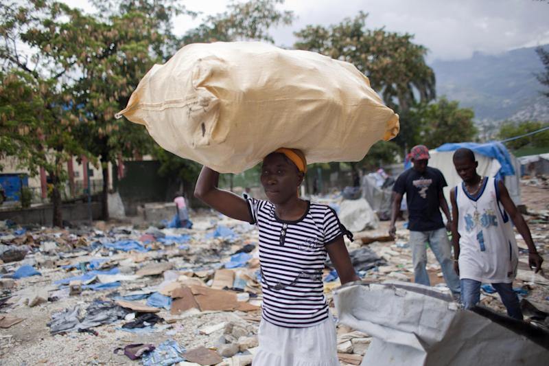 "A woman carries her belongings as she is evicted from a camp that was set up for people displaced by the 2010 earthquake near the national stadium in Port-au-Prince, Haiti, Monday, April 22, 2013. An Amnesty International report says Haiti has violated international human rights obligations by failing to protect people who have been forced to leave the impromptu settlements that sprang up in the Caribbean nation after the 2010 earthquake. People kicked out of settlements find themselves ""further marginalized and driven deeper into poverty,"" it said. (AP Photo/Dieu Nalio Chery)"