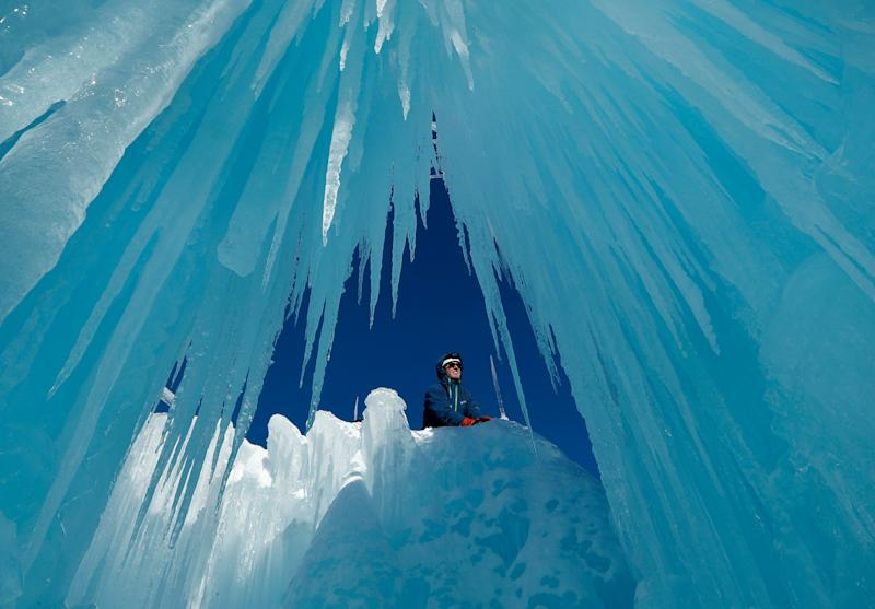 Matt Pasciuto places an icicle at the top of a wall at Ice Castles in North Woodstock, N.H. Slushy snow is used as quick-freezing mortar to hold icicles in place. The spray from sprinklers will help grow the icicles into walls and caverns. (Photo: Robert F. Bukaty/AP)