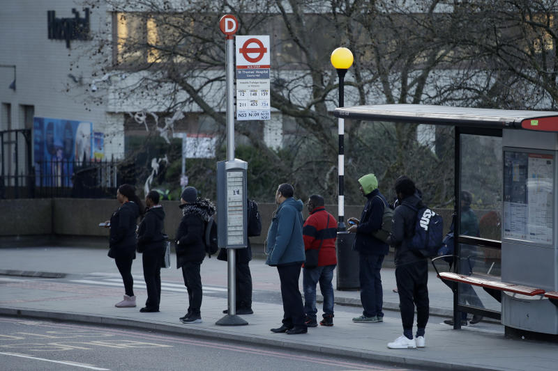 Commuters queue at a bus stop outside St Thomas's Hospital in London, Tuesday, March 24, 2020. For most people, the new coronavirus causes only mild or moderate symptoms, such as fever and cough. For some, especially older adults and people with existing health problems, it can cause more severe illness, including pneumonia. (AP Photo/Matt Dunham)