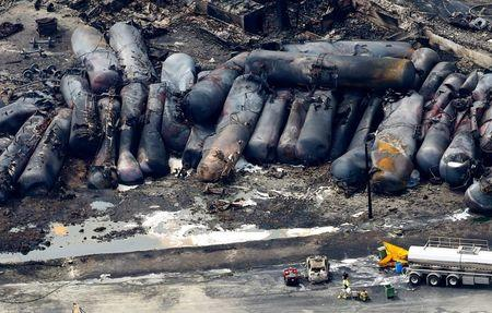 A firefighter stands close to the remains of a train wreckage in Lac Megantic in this file photo