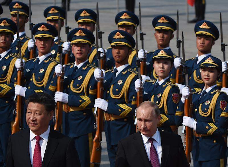 Russia's President Vladimir Putin (bottom R) reviews an honour guard with Chinese President Xi Jinping (bottom L) during a welcoming ceremony in Beijing on June 25, 2016 (AFP Photo/Greg Baker)