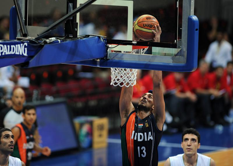 Amjyot Singh (C) of India dunks the ball against Iran in their men's Asian Basketball Championships game in Manila on August 5, 2013