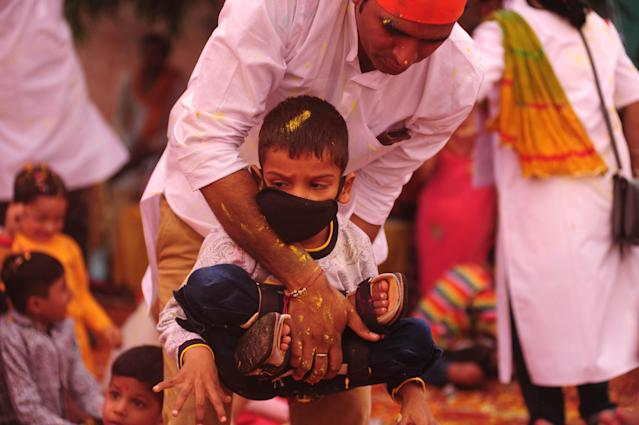 A doctor helps a Child, suffering from Cerebral Palsy, to take part in an event to celebrate the Hindu festival of Holi for the children with cerebral palsy , organised by The Trishla Foundation , in Allahabad on March 6,2020. (Photo by Ritesh Shukla/NurPhoto via Getty Images)
