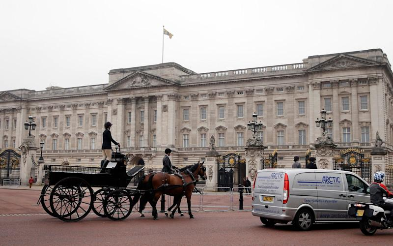 Vehicles and a horse and carriage drive past Buckingham Palace - Credit: AP Photo/Alastair Grant