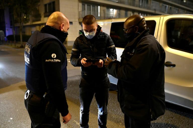 Police officers stop a teenager in Brussels where a curfew is in place