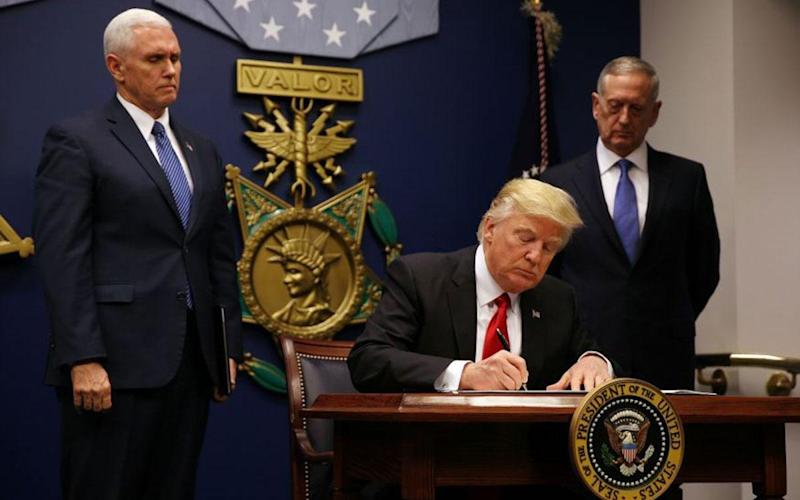 President Trump with Vice President Mike Pence (left) and James Mattis as he signs new order: Reuters