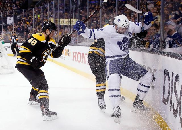 Boston Bruins' Matt Grzelcyk (48) battles Toronto Maple Leafs' Tyler Bozak (42) along the boards during the first period of Game 5 of an NHL hockey first-round playoff series in Boston, Saturday, April 21, 2018. (AP Photo/Michael Dwyer)