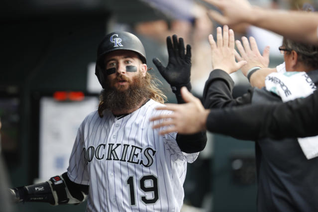 Teammates congratulate Colorado Rockies' Charlie Blackmon as he returns to the dugout after scoring against the San Diego Padres during the second inning of a baseball game Saturday, June 15, 2019, in Denver. (AP Photo/David Zalubowski)