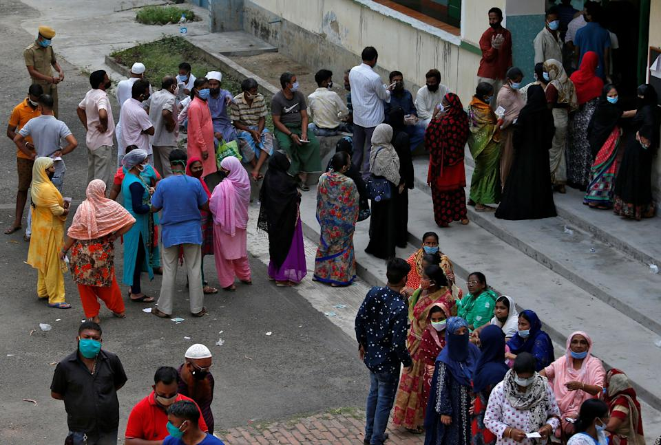 <p>People wait to cast their votes outside a Kolkata polling station during the West Bengal election on Thursday (29 April)</p> (Reuters)
