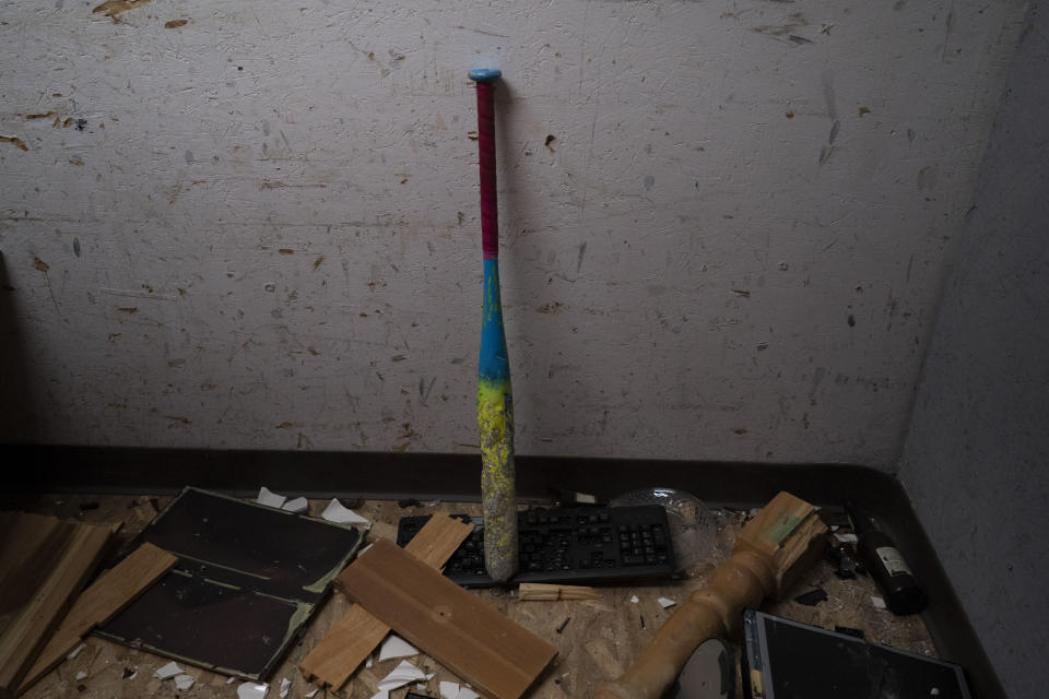 """A baseball bat is propped against a wall in a rage room after clients smashed objects into pieces at Smash RX LLC in Westlake Village, Calif., Friday, Feb. 5, 2021. Meditation, yoga, Pilates, they may be fine for some people. But after nearly a year in COVID-19 isolation, some people just want to grab a sledgehammer and smash everything in sight. Thankfully, for them there are now two """"rage rooms"""" located in the Los Angeles suburb of Westlake Village, where they can do just that and not get in trouble. (AP Photo/Jae C. Hong)"""