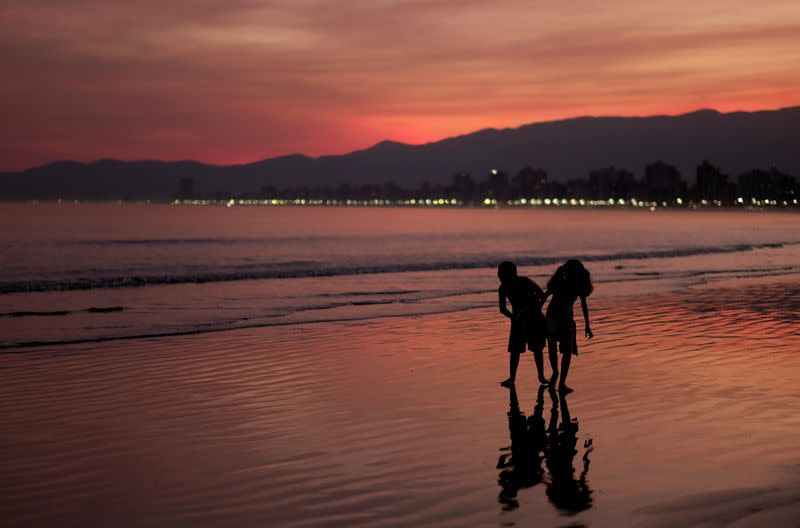 FILE PHOTO: Children walk on a beach during sunset in Praia Grande
