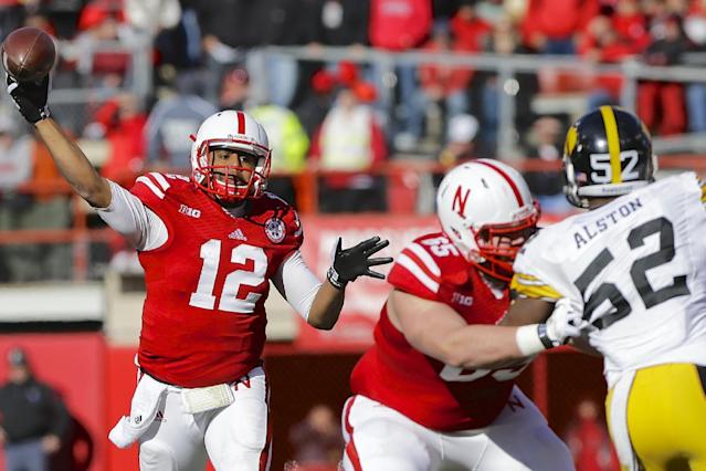 Nebraska quarterback Ron Kellogg III (12) throws a pass as offensive linesman Ryne Reeves (65) blockes Iowa linebacker Quinton Alston (52) during the first half of an NCAA college football game in Lincoln, Neb., Friday, Nov. 29, 2013. (AP Photo/Nati Harnik)