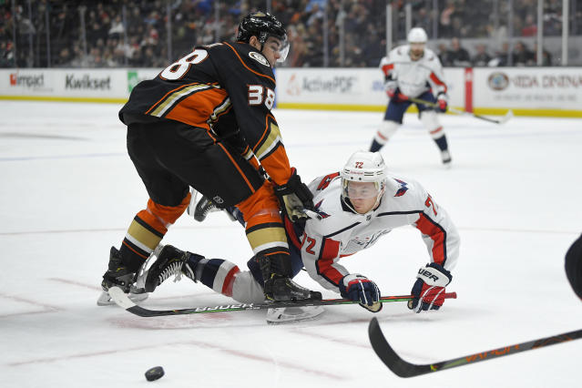 Washington Capitals center Travis Boyd, right, tries to pass the puck while under pressure from Anaheim Ducks center Derek Grant during the first period of an NHL hockey game Friday, Dec. 6, 2019, in Anaheim, Calif. (AP Photo/Mark J. Terrill)