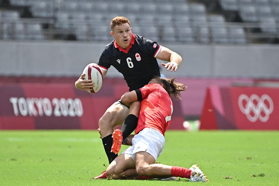 <p>Canada's Connor Braid (L) is tackled by Britain's Dan Bibby (R) in the men's pool B rugby sevens match between Britain and Canada during the Tokyo 2020 Olympic Games at the Tokyo Stadium in Tokyo on July 26, 2021. (Photo by Ben STANSALL / AFP)</p>