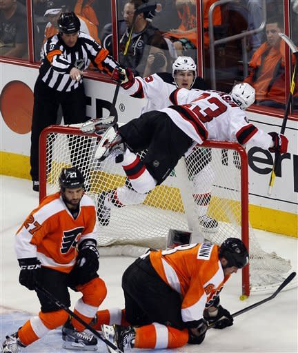 New Jersey Devils' Zach Parise, rear left, goes to David Clarkson, laying on the net, who scored what would be the game-winning goal during the third period in Game 2 of an NHL hockey Stanley Cup second-round playoff series with the Philadelphia Flyers, Tuesday, May 1, 2012, in Philadelphia. Moving away from the net are Flyers Max Talbot, front left,and Nick Grossmann The Devils won 4-1 tying the best of seven series at 1-1.(AP Photo/Tom Mihalek)