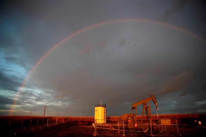 A rainbow is seen over a pumpjack during sunset outside Scheibenhard