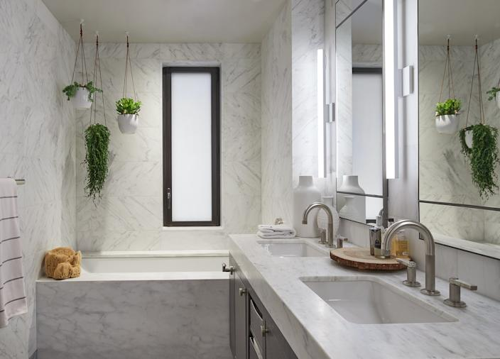 "<div class=""caption""> The master bath is clad in Carrera marble, with sink faucets from <a href=""https://www.kallista.com/"" rel=""nofollow noopener"" target=""_blank"" data-ylk=""slk:Kallista"" class=""link rapid-noclick-resp"">Kallista</a>. The plant hangers came from just up the street from a supplier in the Flower District. </div>"