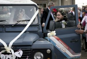 "Actors Kit Harington and Rose Leslie react as they leave after their wedding ceremony, at Rayne Church, Kirkton of Rayne in Aberdeenshire, Scotland, Saturday June 23, 2018. Former ""Game of Thrones"" co-stars Kiet Harington and Rose Leslie married near the bride's family castle in Scotland. The couple and guests arrived at Rayne Church, close to the 900-year-old Wardhill Castle in northeast Scotland, which is owned by Leslie's family. Harington, wearing a morning suit, and Leslie, in a flowing ivory gown, smiled at members of the public who had gathered outside the church. (Jane Barlow/PA via AP)"