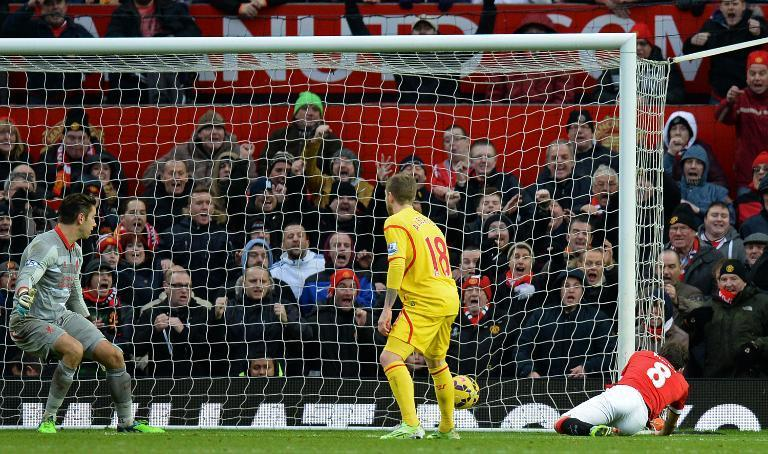 Manchester United's Spanish midfielder Juan Mata (R) scores their second goal as Liverpool's Australian goalkeeper Brad Jones (L) looks on during the English Premier League football match at Old Trafford on December 14, 2014 (AFP Photo/Oli Scarff)