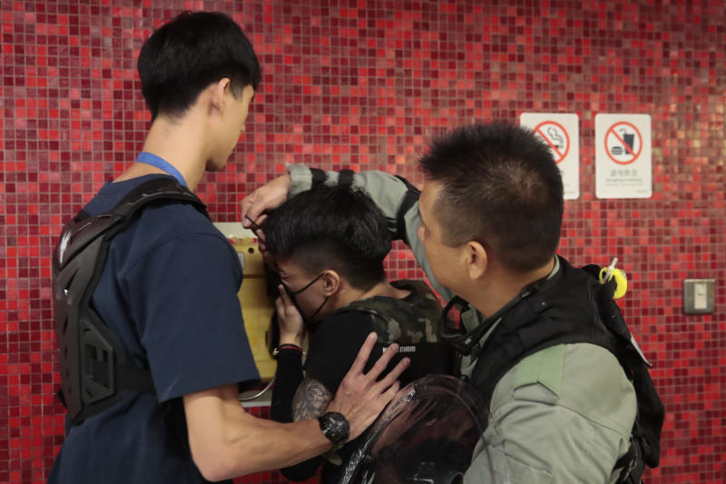 Police remove the face mask of a protesters after he blocked train door at a subway station in Hong Kong, on Monday, Sept. 2, 2019. Hong Kong has been the scene of tense anti-government protests for nearly three months. The demonstrations began in response to a proposed extradition law and have expanded to include other grievances and demands for democracy in the semiautonomous Chinese territory. (AP Photo/Jae C. Hong)