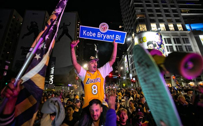 Amid a throng of people, a man seated on another man's shoulders holds a Kobe Bryant Boulevard sign.