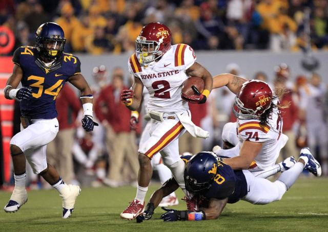 Iowa State's Aaron Wimberly (2) slips a tackle by West Virginia's Karl Joseph (8) during the second quarter of an NCAA college football game in Morgantown, W.Va., on Saturday, Nov. 30, 2013. (AP Photo/Christopher Jackson)