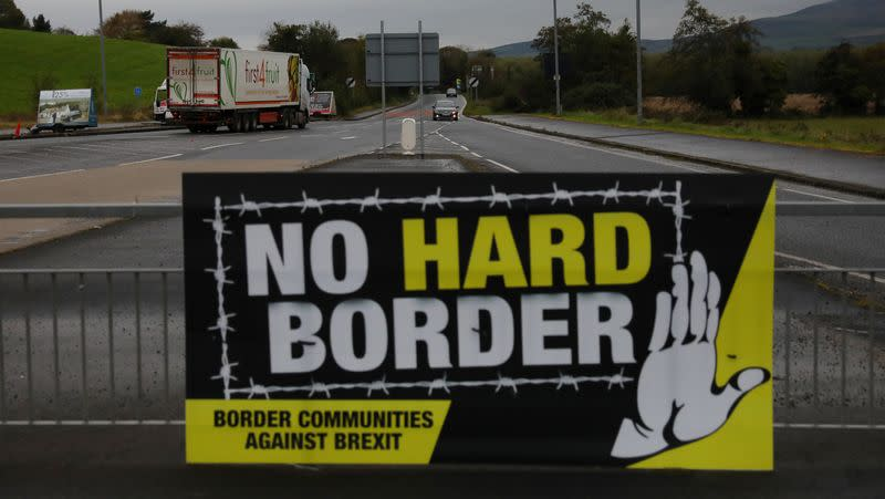A lorry drives past a 'No Hard Border' poster near Londonderry, Northern Ireland