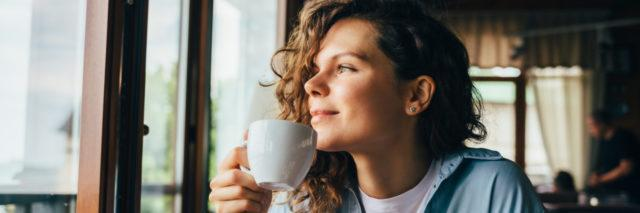 Woman drinking coffee and looking out the window, sitting at table.