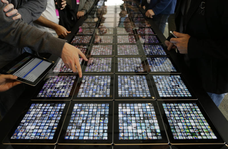 Developers look over new apps being displayed on iPads at the Apple Worldwide Developers Conference Monday, June 10, 2013 in San Francisco. (AP Photo/Eric Risberg)