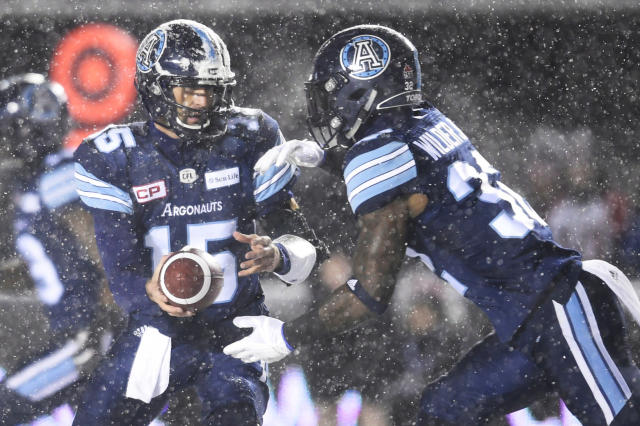Toronto Argonauts quarterback Ricky Ray (15) hands the ball off to Toronto Argonauts running back James Wilder Jr. (32) during the first half of a CFL football game in the Grey Cup in Ottawa on Sunday, Nov. 26, 2017. (Nathan Denette/The Canadian Press via AP)