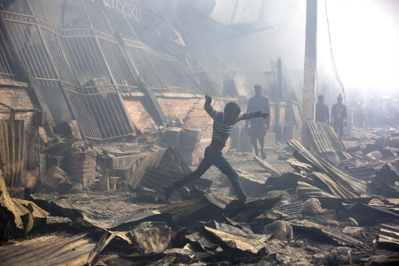 A boy jumps over debris outside the Iron Market, also known as Marche Hyppolite, in the aftermath of a massive fire that swept through a section of the popular marketplace, in Port-au-Prince, Haiti, Tuesday, Feb. 13, 2018. Police said Tuesday they are still trying to determine the cause of late-night blaze that ravaged the principal market, and said they were not aware of any deaths or injuries. (AP Photo/Dieu Nalio Chery)