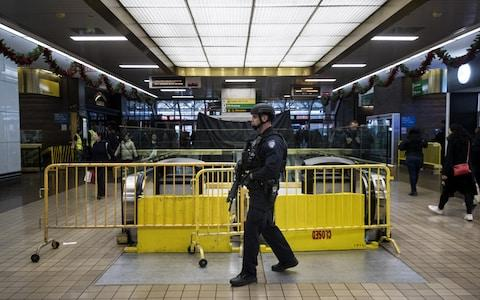 A member of the New York City Police Department stands guard inside the New York Port Authority Bus Terminal after it reopened - Credit: Getty
