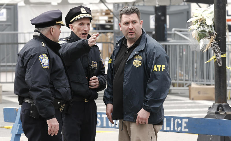 With flowers tied to a light pole next to them, Boston Police Superintendent William Evans, center, talks with an ATF agent at a barricade near the finish line of the Boston Marathon in Boston Tuesday, April 16, 2013. The bombs that ripped through the Boston Marathon crowd were fashioned out of ordinary kitchen pressure cookers, packed with nails and other fiendishly lethal shrapnel, and hidden in duffel bags left on the ground, people close to the investigation said Tuesday. (AP Photo/Winslow Townson)