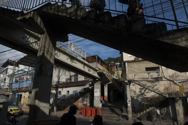 """In this Aug. 14, 2013 photo, pedestrians walk in the Borel favela, in Rio de Janeiro, Brazil. In slums that have undergone police """"pacification,"""" with officers pushing out gangs and setting up permanent posts, a dance form called """"passinho,"""" or """"little step,"""" has sprung up to replace the more raucous """"baile funk"""" gatherings. (AP Photo/Nicolas Tanner)"""