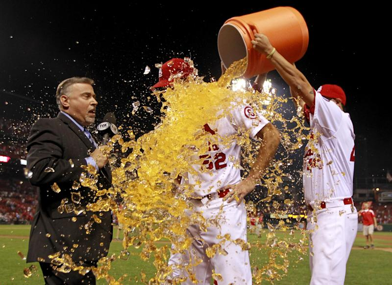 St. Louis Cardinals starting pitcher Michael Wacha is dunked by teammates Edward Mujica, right, and John Axford, while being interviewed by broadcaster Jim Hayes, left, following a baseball game against the Washington Nationals Tuesday, Sept. 24, 2013, in St. Louis. Wacha gave up a no-hitter with two outs in the ninth inning and the Cardinals won 2-0. (AP Photo/Jeff Roberson)