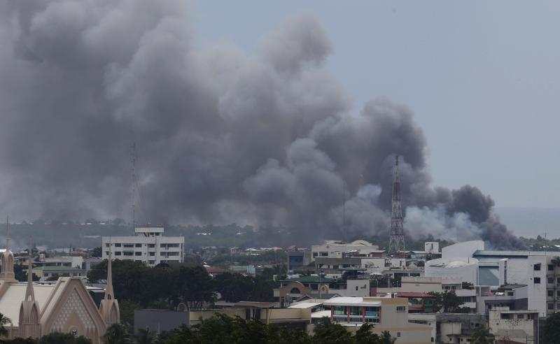 Smoke billows from downtown Zamboanga city as fighting rages between government soldiers and the Muslim rebels of the Moro National Liberation Front (MNLF), in southern Philippines September 19, 2013. Police said the death toll in the fighting between the soldiers and the rebels has reached 104, and around 110,000 have been displaced. REUTERS/Erik De Castro (PHILIPPINES - Tags: CIVIL UNREST MILITARY POLITICS)