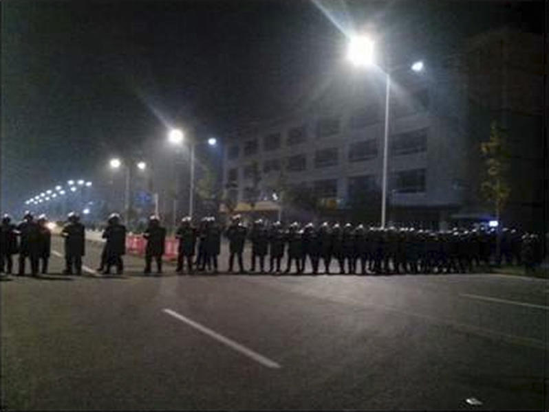In this Monday Sept. 24, 2012 mobile phone photo, police in anti-riot suits cordon off a road near Foxconn's plant in Taiyuan, capital of Northern China's Shanxi province. The company that makes Apple's iPhones suspended production at a factory in China on Monday after a brawl by as many as 2,000 employees at a nearby dormitory injured 40 people. The facility will reopen Tuesday. (AP Photo) CHINA OUT
