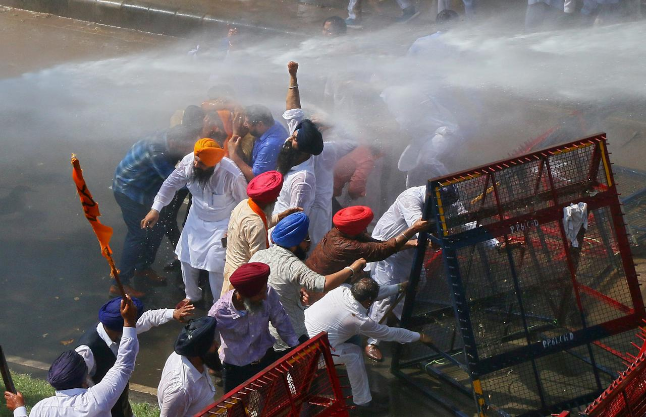 Demonstrators are hit by police water cannon during a protest, organised by Punjab's main opposition party Shiromani Akali Dal (SAD), demanding debt waiver of farmers in Chandigarh, India, March 20, 2018. REUTERS/Ajay Verma