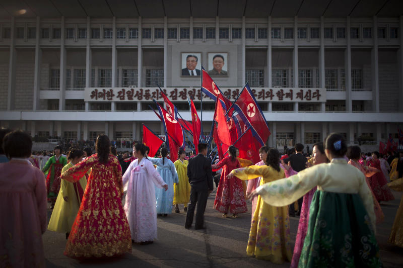 A man, center, supervises a dancing group  during a mass folk dance in front of the Pyongyang Indoor Stadium in Pyongyang, North Korea, Monday, April 15, 2013. Oblivious to international tensions over a possible North Korean missile launch, Pyongyang residents spilled into the streets Monday to celebrate a major national holiday, the birthday of their first leader, Kim Il Sung. (AP Photo/Alexander F. Yuan)