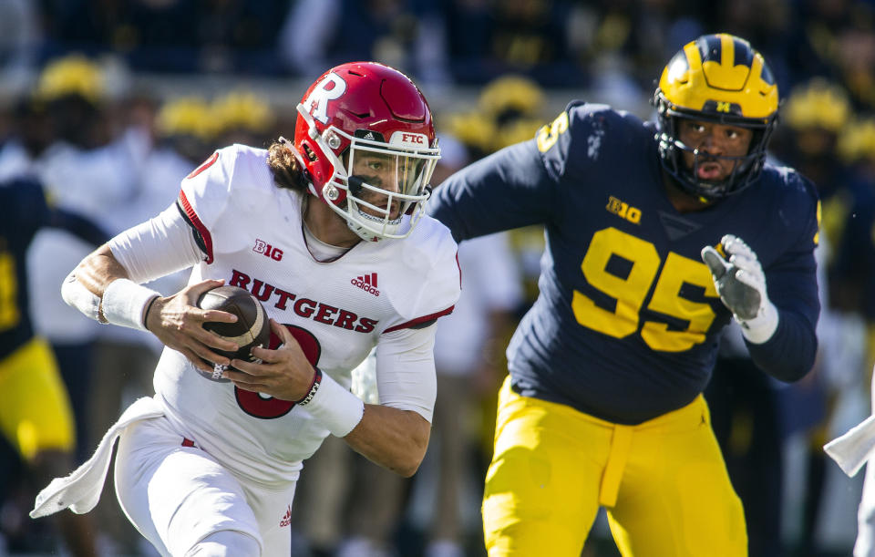 Rutgers quarterback Noah Vedral, left, scrambles away from Michigan defensive lineman Donovan Jeter (95) in the second quarter of an NCAA college football game in Ann Arbor, Mich., Saturday, Sept. 25, 2021. (AP Photo/Tony Ding)
