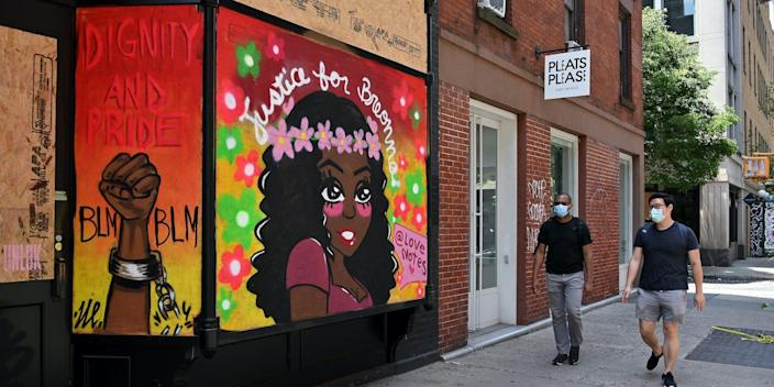 """People walk past a mural reading """"Justice for Breonna"""" on a Prince Street storefront, on June 19, 2020."""