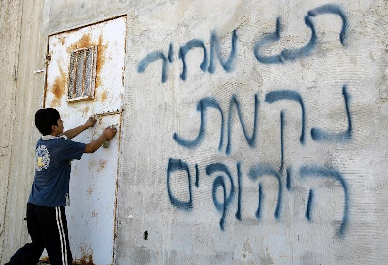 File picture shows a Palestinian boy going into a building on which Hebrew graffiti has been daubed, allegedly by Jewish settlers, in the Israeli occupied Palestinian West Bank