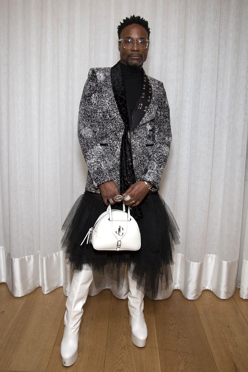 <p>The actor wore a black tulle skirt, white platform thigh-high boots and a monochrome printed blazer to the Matty Bovan fashion show at London Fashion Week February. The star styled the look with a white patent bag. </p>