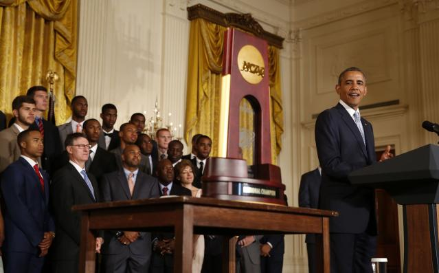 U.S. President Barack Obama looks at the trophy as he honors team members of the 2014 NCAA champion UConn Huskies men's and women's basketball teams while in the East Room of the White House in Washington, June 9, 2014. REUTERS/Larry Downing (UNITED STATES - Tags: POLITICS SPORT BASKETBALL)
