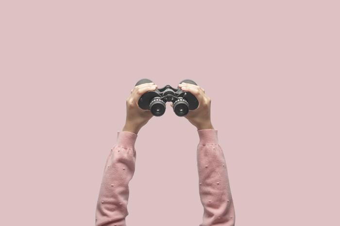 A pair of hands extended holding binoculars.