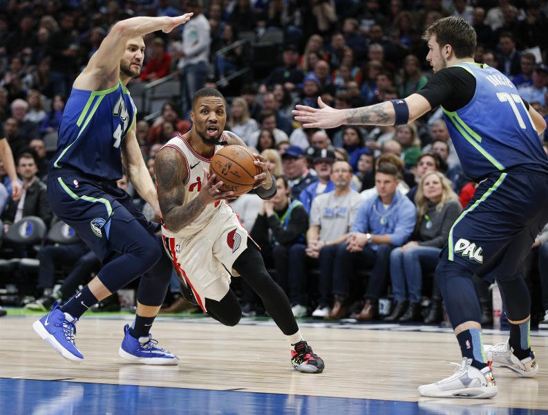 Portland Trail Blazers guard Damian Lillard, center, drives between Dallas Mavericks forwards Maxi Kleber, left, and Luka Doncic during the second half of an NBA basketball game, Friday, Jan. 17, 2020, in Dallas. The Mavericks won 120-112. (AP Photo/Brandon Wade)