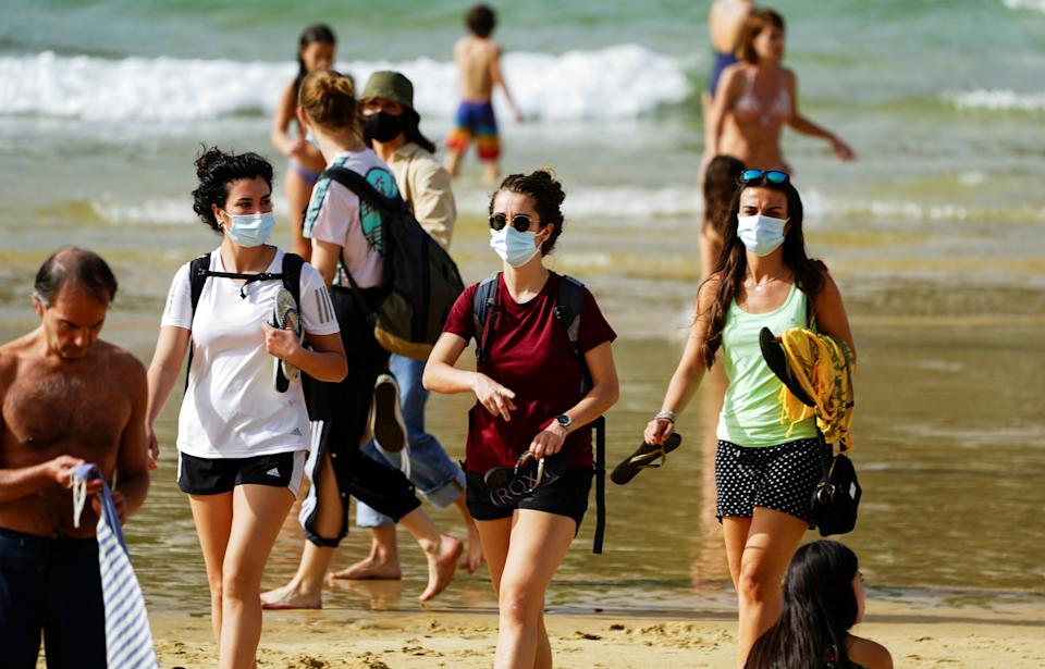 People wear masks at La Concha beach after Spain introduced stricter mask laws during the coronavirus disease (COVID-19) outbreak, in San Sebastian, Spain, March 31, 2021. REUTERS/Vincent West
