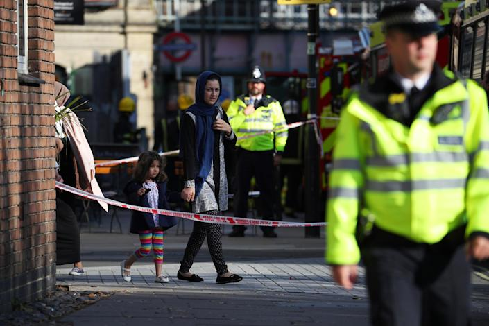 <p>A woman walks with her child past police cordon near Parsons Green tube station in London, Britain, Sept. 15, 2017. (Photo: Hannah McKay/Reuters) </p>